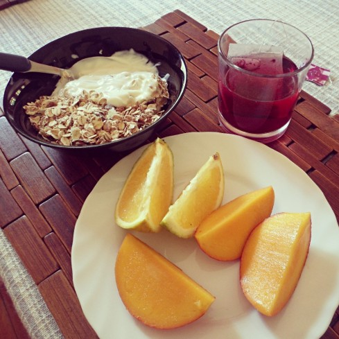Muesli with honey and natural yoghurt, oranges, mango and hibiscus tea